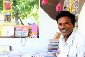 Illiterate man helping students with books